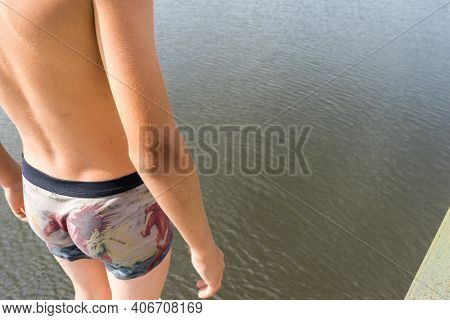 Boy Relaxes On A Tower For Jumping Into Water. Boy Resting Near The Lake. Swimmer In Shorts. Summer
