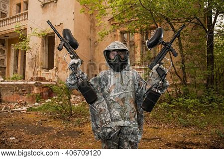 Young Man Playing Paintball. Boy In Camouflage Clothing Aiming A Paintball Gun. Boy In A Protective