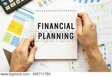Businessman Hold Notepad With Text Financial Planning. Financial Charts On The Desktop. Financial An