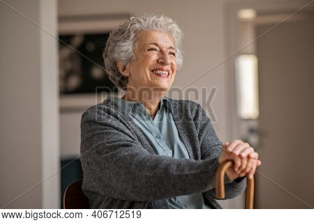 Retired senior woman laughing while relaxing at home. Happy smiling old woman holding walking cane and looking through the window with positivity. Carefree grandmother sitting on chair in nursing home