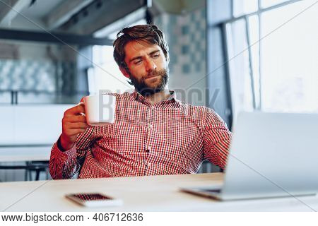 Puzzled Thoughtful Businessman Sitting At His Working Table In An Office