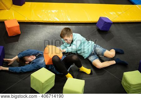 Happy Smiling 11 Years Old Kids Jumping On Trampoline Indoors In Entertainment Center. Active Childr