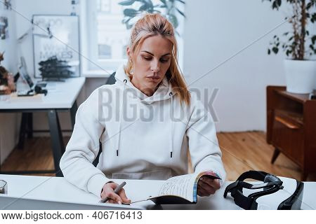 Female Businessperson In White Hoody Does Her Job In Comfortable Office Using A Laptop.