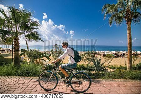 Turkey, Alanya - October 20, 2020:Young man with a protective mask rides a bicycle on Alanya promenade - Ahmet Tokus Bul. in Alanya, Turkey