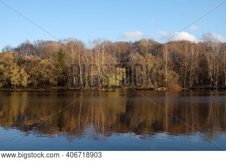 Calm Countryside Landscape With Quite River And Autumn Colored Forest After It Under Clear Blue Sky