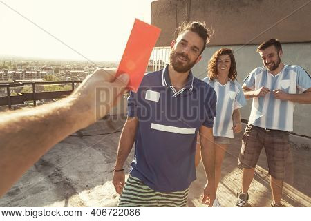 Group Of People Playing Football, Referee Giving A Red Card To One Of The Players After A Foul; Peop