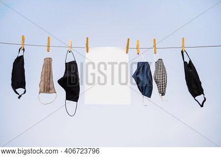 Many Protective Masks Hanging On The Rope With An Empty Sheet Of Paper