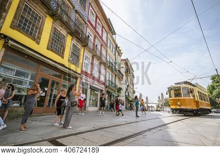 Tourists Taking Photographs Of Approaching Vintage Tram In Porto, Portugal