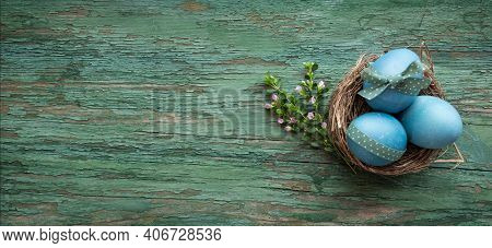 Pastel Blue Colored Easter Eggs On Green Shabby Wood. Country Style Easter Decoration With Flowers.