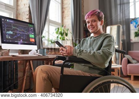 Disabled Woman With Short Hair Sitting On Wheelchair And Working Online On Mobile Phone During Her W