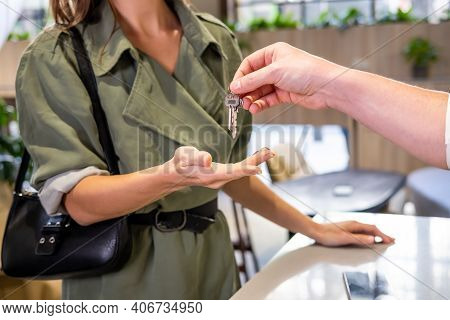 Selective Focus At Men Hand And Key. Hotel Staff Welcome Visitor And Giving Room Key To  Women Guest