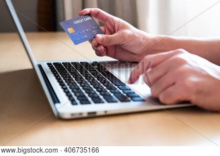 Men Hand Holding Credit Card And Type Payment Information On Keyboard For Order Online Shopping. Int
