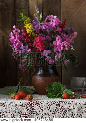 Dark Rustic Still Life. Flowers And Berries. Bouquet Of Phlox And Snapdragon In A Jug And Strawberri