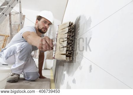 Construction Worker Painter Man With Protective Helmet, Brush In Hand Restores And Paint The Wall, I