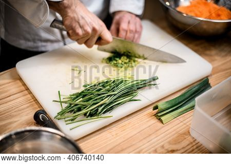 Male Hands Chopping Salad Scallion Ingredient. Chef Cutting Green Onion With Sharp Knife.