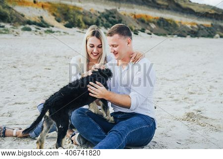 A Beautiful, Attractive, Loving Couple Playing With Mutts On The Seashore. Lovers, Wearing White Coa