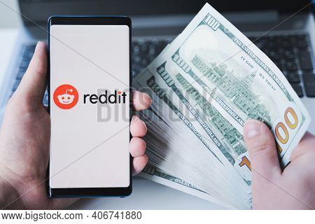 Russia Moscow 02.02.21 Mobile Phone With Logo Of Reddit Traders, Money,dollars In Hands.community Of