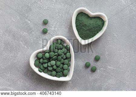Green Algae In Powder And Pills - Chlorella, Spirulina A Gray Background. Healthy Green Food Supplem
