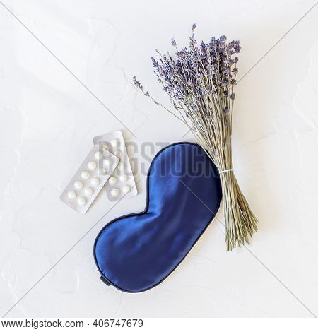 Flat Lay Composition With Lavender Flowers, Mask For Sleep And Sleeping Pills At Once On A White Bac