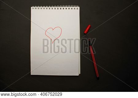 A Red Marker With A White Notebook On A Black Background. View From Above. Colorful Pens With A Larg