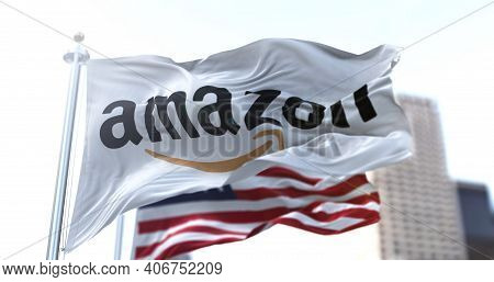 Seattle, Wa, Usa, January 28, 2021: Flag With The Amazon Logo Waving In The Wind With The American F
