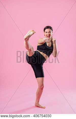 Slim Woman Kicking The Air, With Hand And Leg Up. Athletic Girl Doing Boxing Exercises, Making A Dir