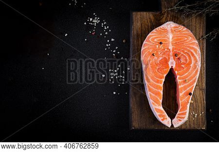 Salmon. Raw Fish Salmon Steak Fillet With Cooking Ingredients, Herbs And Lemon On Black Background W