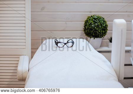 White Medical Chair With Black Glasses For Hair Removal Procedure And Green Plant With Wooden Wall.