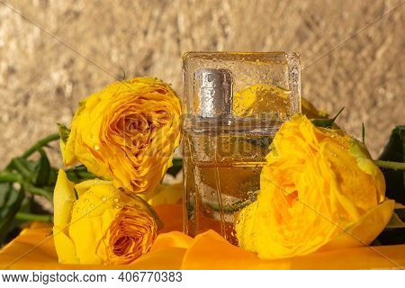 Close-up Of Perfume Glass Bottle With Wet Drops. Beautiful Orange Roses In Raindrops. Composition Of