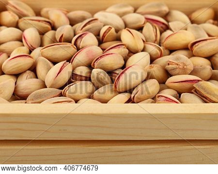 Background Texture Of Fresh Roasted Pistachio Nuts In Wooden Box, Elevated, High Angle View