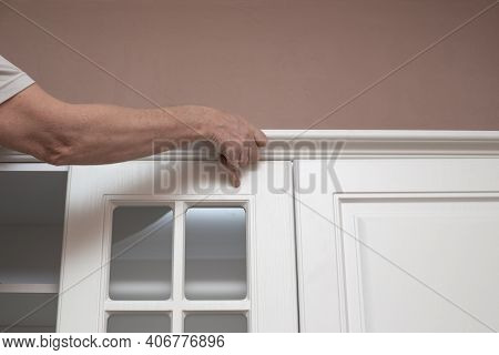 Furniture Assembly. The Man Assembles The Kitchen Set, Attaches The Cornice To The Upper Cabinets.
