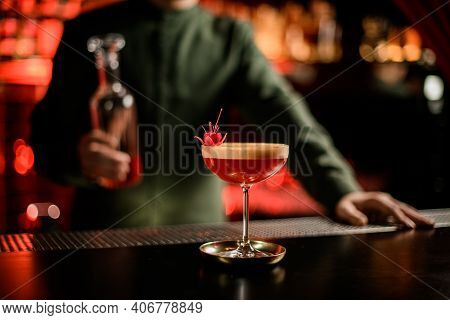 View Of Beautiful Glass With Red Foamy Alcoholic Drink Decorated With Flower On Bar