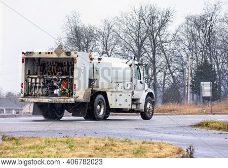 Horizontal Shot Of A Lubrication Service Truck From The Rear Driving In Rain And Snow.