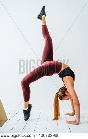 Young Slim Sporty Woman Showing Gymnastics Or Yoga Pose Bridge With Leg Up In The Air. Training At H