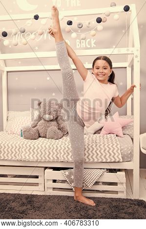 Improve Flexibility. Girl Child Split In Bedroom. Kid Prepare Go To Bed. Girl Cute Pajamas Relaxing
