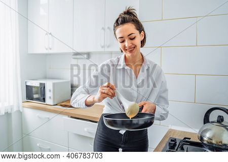 Woman Pours The Dough Into A Pan To Cook Homemade Fried Banana Pancakes. Hobby In A Beautiful Bright