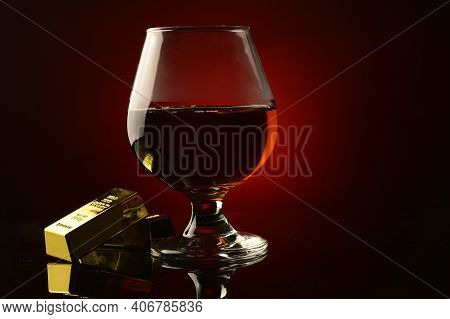 A Concept Of Wealth Utilizing A Couple Gold Bullion Bars Next To A Rich Cognac Drink Over A Dark Ref