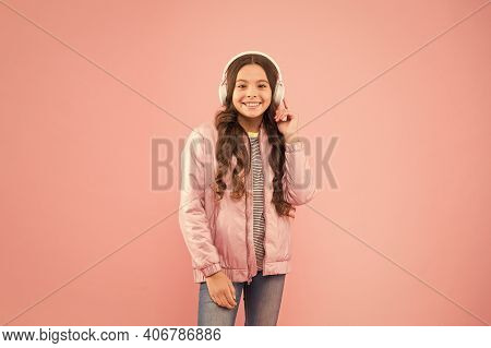 Hipster Style Everyday. Little Girl Wear Earphones Pink Background. Sound Vibrations. Music And Tech