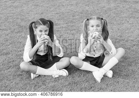 Schoolgirls Eating Apples Relaxing Schoolyard, Healthy Lunch Concept.