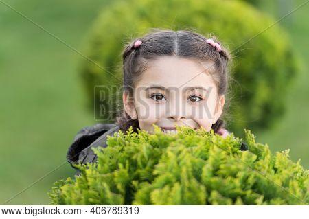 Hide And Seek Fun. Girl Cute Smiling Kid Green Grass Background. Healthy Emotional Happy Kid Relaxin