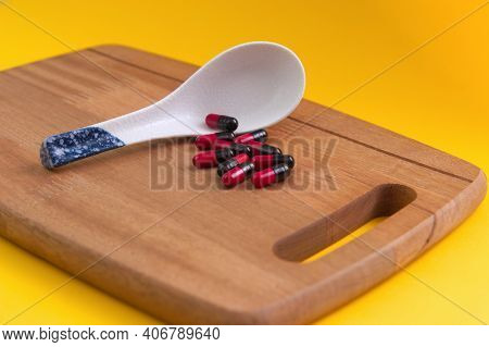 Pharmaceutical Medicine Pills Spilled From Porcelain Spoon Placed On A Chopping Board With Isolated
