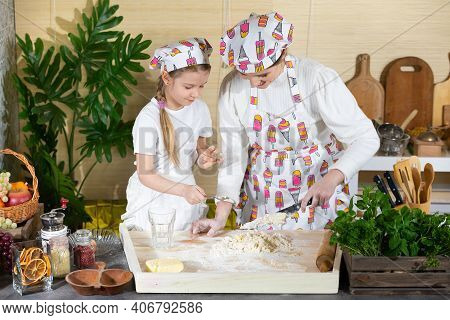 Mixing Dough With A Kitchen Knife And Teaspoon It On One Table In The Kitchen By Mom And Daughter. T