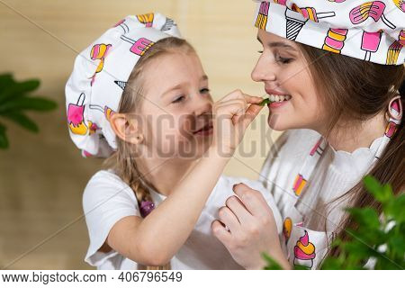 A Five-year-old Daughter Decided To Give Her Mother One Basil Leaf To Try. The Joy Of Mom And Daught
