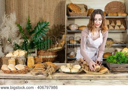 Before The Arrival Of The First Customers, A Young Attractive Saleswoman Arranges The Bread At Her C