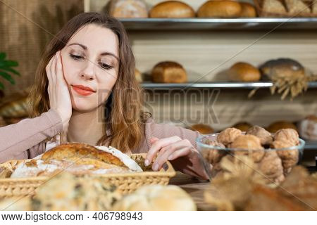 After Opening A Bakery Shop, The Saleswoman Waits For Her Customers. The Saleswoman Is Examining The