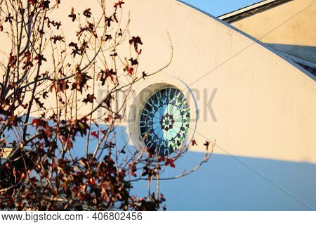 February 5, 2021 In Whittier, Ca:  Historical Church With A Stained Glass Window Besides A Liquid Am