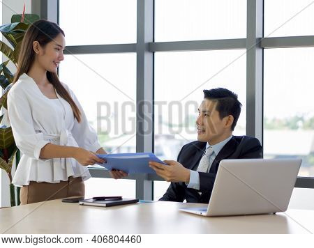 Managing Director In Suit Returns Document Folder To Secretary With An Impression After The Project