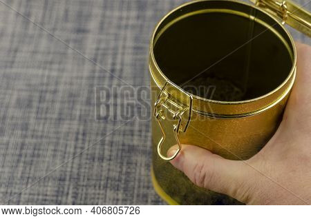 A Man's Hand Holding An Open Tea Coffee Tin With A Clasp Close-up. Gold Latch Lock Tin For Dry Goods