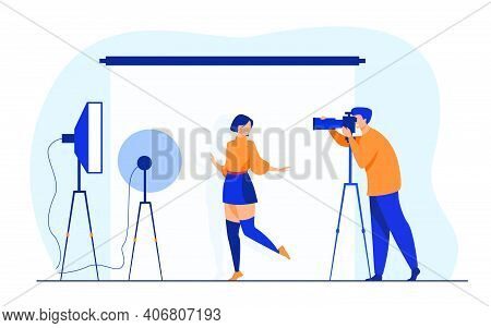Professional Photographer Taking Pictures Of Young Woman. Female Model Posing For Camera Against Whi