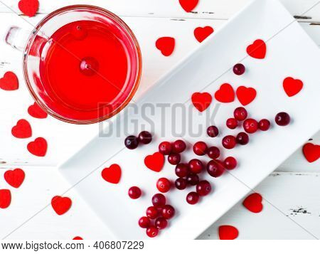 Selective Focus On Cranberries In A Red Drink In A Glass Cup On A Wooden White Background. Many Smal